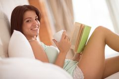 Rested girl drink morning coffee and read interesting book. Well rested girl drink morning coffee in bed and read interesting book with smile Stock Image