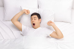 Rested man waking up in a bed. Young rested man waking up in a comfortable bed and stretching himself Royalty Free Stock Image