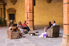 Rested people on a stone bench in the courtyard in Bologna. Bologna, Italy - August 18, 2014: People resting on a stone bench in the courtyard of the Palazzo Stock Photo