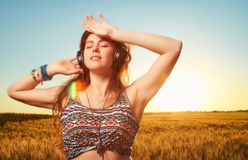 Rested young athletic woman with closed eyes,  listening to musi. C with headphones  with bracelets on the arm, on a sunset background in a wheat field Stock Photo