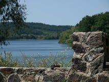 Resten van steenbouw op de achtergrond van de rivier en het bos stock afbeeldingen