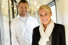 Rester de sourire de femme et d'homme dans le train Photos stock