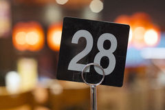 Restaurant table number. Closeup of a restaurant table number 28 with bokeh lights in background royalty free stock images
