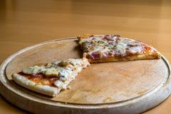 Resterende pizzastukken op een houten scherpe raad Stock Afbeeldingen