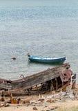 Restes d'un bateau abandonné détruit sur le rivage, un symbole de décadence et de dégradation, et canot automobile moderne photo libre de droits