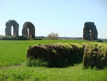Restes d'un vieil aqueduc romain à un vert d'étendue des pelouses dans le pays romain à jaillir l'Italie photo stock