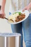 Restes de éraflure de nourriture de femme dans la poubelle de déchets photos libres de droits