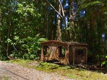 Restes de extraction rouillés sur le passage couvert de charme de crique, Nouvelle-Zélande photographie stock