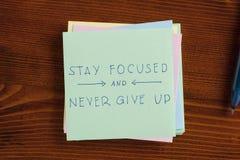 Restez focalisé et n'abandonnez jamais écrit sur la note Image stock