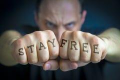 RESTEZ FREE écrite sur les poings fâchés de man's Photo stock