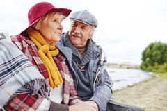 Restful aged couple. Retired couple in warm clothes having outdoor rest Royalty Free Stock Photography