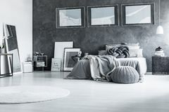 Restful black and white bedroom. White carpet and pouf in restful black and white bedroom with king-size bed posters and mirror Stock Photography