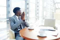 Restful businessman. Inspired businesman sitting by table at coffee-break Royalty Free Stock Photo