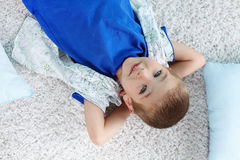 Restful child. Cute kid lying on the floor with his hands behind his head Royalty Free Stock Photography