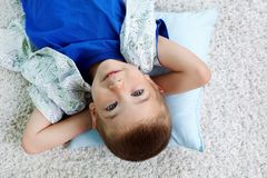 Restful child. Cute kid lying on the pillow with his hands behind his head Stock Photos