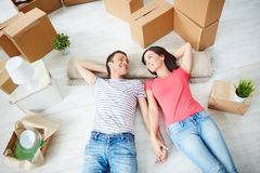 Restful couple. Happy young couple lying on the floor of new house and looking at one another Royalty Free Stock Photography