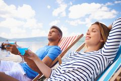 Restful couple. Serene dates with martini relaxing at summer resort Royalty Free Stock Photos