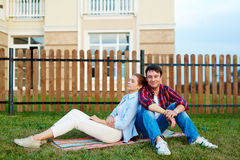 Restful couple. Young couple having rest on green lawn by their new house Royalty Free Stock Photo