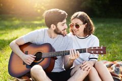Restful couple of young people having relaxation outdoors enjoying pleasant moments and calm atmosphere. Romantic male with beard. Holding guitar playing to his Royalty Free Stock Photography