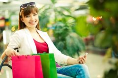 Restful customer. Pretty lady with colorful shopping bags sitting in trade center Stock Image