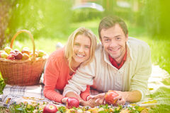 Restful dates. Happy young couple with ripe apples having rest in park Stock Images