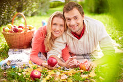 Restful dates. Happy young couple with ripe apples having rest in park Royalty Free Stock Image