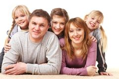 Restful family. A young friendly family looking at camera on white background Royalty Free Stock Photo