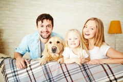 Restful family. Happy young couple, their daughter and dog enjoying weekend Royalty Free Stock Images
