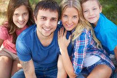 Restful family. Photo of happy family of four looking at camera outdoors Stock Photos