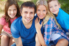 Restful family. Photo of happy family of four looking at camera outdoors Stock Images