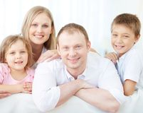Restful family. Portrait of happy parents with two children looking at camera at home Stock Photos
