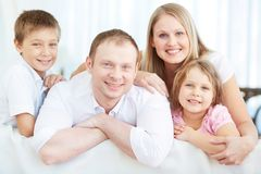 Restful family. Portrait of happy parents with two children looking at camera at home Stock Images