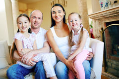 Restful family. Smiling family of four sitting on sofa at home Stock Images