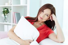 Restful female. Portrait of a smiling woman looking at camera while resting at home Stock Photos