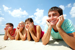 Restful friends. Four young friends lying on sand and smiling Royalty Free Stock Photography