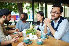 Restful friends. Restful guys and girl talking by cup of tea Stock Photo