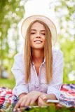 Restful girl. Happy girl in hat looking at camera while relaxing outside Stock Image
