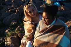Restful girls. Intercultural girls spending summer evening by talk on the beach Royalty Free Stock Image
