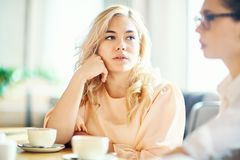 Restful girls. Pretty blonde girl listening to her friend by cup of coffee in cafeteria Royalty Free Stock Photography