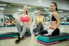 Restful girls. Three cheerful girlfriends in activewear looking at camera while sitting on step platforms after training Stock Photos