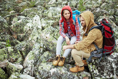 Restful hikers. Adventurous couple having rest on stones during hike Stock Images