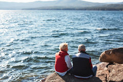Restful hikers. Aged couple sitting on stone by lake and talking Stock Photography