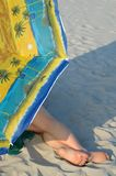 Restful holiday. A girl lying on the beach in the shade of the parasol during a hot day Royalty Free Stock Images