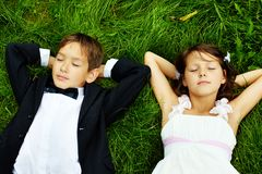 Restful kids. Portrait of calm children bride and groom lying on green grass Royalty Free Stock Images