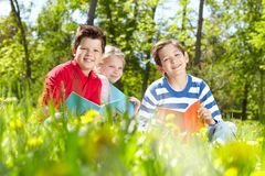 Restful kids. Three friends looking at camera while reading on the lawn Royalty Free Stock Photography