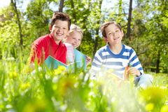 Restful kids. Three friends looking at camera while reading on the lawn Royalty Free Stock Photo