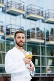 Restful man. Calm young man with glass of drink wearing white bathrobe while relaxing Stock Images