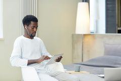 Distant learning. Restful man in homewear watching video in touchpad at leisure Stock Photography