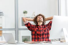 Restful man. Pensive man looking at ceiling while sitting by workplace in front of computer Royalty Free Stock Photos
