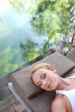 Restful moment by natural pool. Portrait of woman relaxing in deck chair Royalty Free Stock Photography